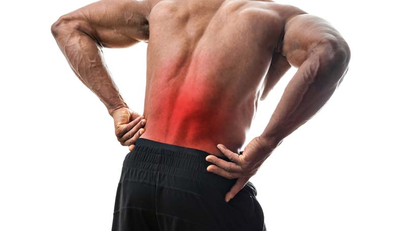 Fit man or athlete reaching for his lower back in pain with the painful area highlighted in red.